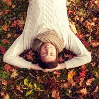 57595939 - season, happiness and people concept - smiling young man lying on ground or grass and fallen leaves in autumn park
